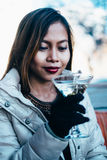 Beautiful adult girl drinking Martini outdoor , early spring. Young woman drinking martini in a cold weather outdoor Royalty Free Stock Images
