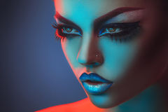 Beautiful adult girl looking away with red and blue lights Royalty Free Stock Photography