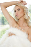 Beautiful adult sensuality woman. Portrait of beautiful young adult sensuality blonde woman wrapped in white fur Royalty Free Stock Photography