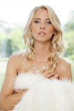 Beautiful adult sensuality woman. Portrait of beautiful young adult sensuality blonde woman wrapped in white fur Stock Photo