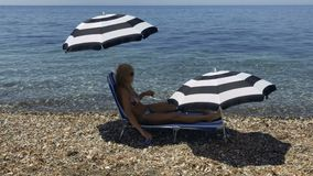 Beautiful adult woman in bikinin lays on deck chair at the beach and drink water. Wet tanned woman in bikini and sunglasses comes out from the sea. Young woman stock footage
