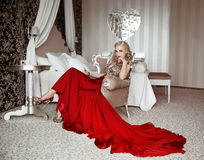 Beautiful adult woman in fashion red dress sitting on modern arm Royalty Free Stock Images