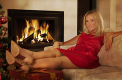 Beautiful adult woman by fireplace at home Royalty Free Stock Photography