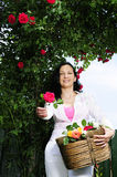 Beautiful adult woman giving a rose in garden Royalty Free Stock Photos