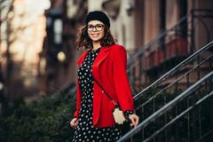 Beautiful adult woman leaves house and walking to the work smiling and enjoying the new day wearing classic red jacket, hat. Eyeglasses and black dress with Stock Images