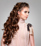 Beautiful adult woman with long brown curly hair. Fashion model posing at studio royalty free stock photography