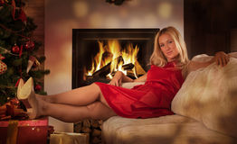 Beautiful adult woman, looking at camera, by fireplace at home Stock Photo