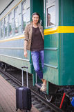 Beautiful adult woman on the steps of the passenger car Royalty Free Stock Image