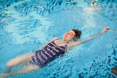 Beautiful adult woman in striped swimsuit swimming in blue pool on her back at resort. Sport activity health concept. Beautiful adult woman in striped swimsuit royalty free stock photo
