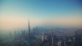 Beautiful aerial drone flight over futuristic tower Dubai downtown skyscrapers in foggy morning sunrise. Aerial drone flight over futuristic tower Dubai downtown stock video footage