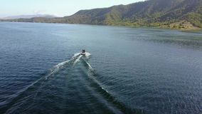 Beautiful 4k aerial drone view on person water skiing attached to motor boat in tropical ocean mountain skyline seascape. Beautiful aerial drone view on person stock video footage
