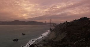 Establishing shot of the Golden Gate Bridge. Beautiful aerial establishing shot of the Golden Gate Bridge in San Francisco, California at sunset stock footage