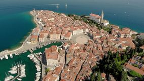 Beautiful aerial video of Piran town with Tartini main square, ancient buildings with red roofs and Adriatic sea in stock video