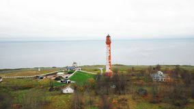 Beautiful aerial panning shot of scenic old lighthouse and buildings on picturesque overcast sea shore on cloudy day. Drone is panning around wonderful stock footage