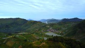 Beautiful scenery mountain valley in Dieng Plateau. Beautiful aerial scenery footage of mountain valley with farmland, lake, and village in Dieng Plateau stock footage