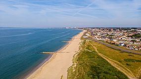 A beautiful aerial  seaside view with sandy beach, crystal blue water, groynes breakwaters and green vegetation dunes along a. Town under a majestic blue sky royalty free stock photos