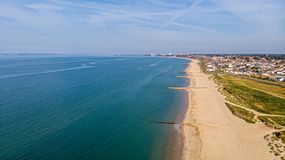 A beautiful aerial  seaside view with sandy beach, crystal blue water, groynes breakwaters and green vegetation dunes along a. Town under a majestic blue sky royalty free stock photography