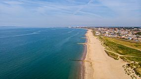 A beautiful aerial  seaside view with sandy beach, crystal blue water, groynes breakwaters and green vegetation dunes along a. Town under a majestic blue sky royalty free stock photo