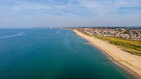 A beautiful aerial  seaside view with sandy beach, crystal blue water, groynes breakwaters and green vegetation dunes along a. Town under a majestic blue sky royalty free stock image