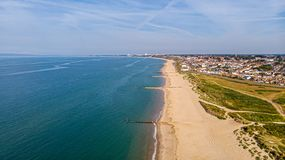 A beautiful aerial  seaside view with sandy beach, crystal blue water, groynes breakwaters and green vegetation dunes along a. Town under a majestic blue sky stock photo