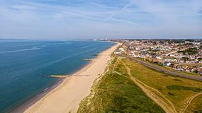 A beautiful aerial  seaside view with sandy beach, crystal blue water, groynes breakwaters and green vegetation dunes along a. Town under a majestic blue sky stock image