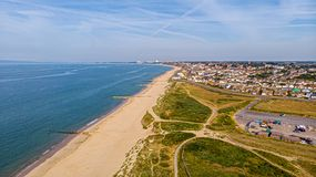 A beautiful aerial  seaside view with sandy beach, crystal blue water, groynes breakwaters, green vegetation dunes and parking. Along a town under a majestic royalty free stock photography