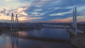 Beautiful aerial view of cable-stayed bridge across the Neva river. Cable-Stayed Bridge in St.Petersburg at sunset. Go over the bridge cars. Aerial view from the stock footage