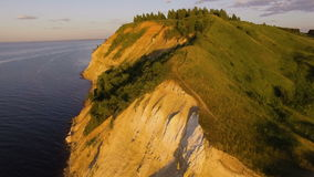 Beautiful aerial view of cliff with trees and grass on the river`s edge.  stock video