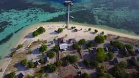 Aerial view of Kanawa Island Resort. Beautiful aerial view footage of Kanawa Island resort with bungalows, wooden jetty, boats, and turquoise water close to stock video