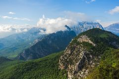 Beautiful aerial view at green woody hills of mountains in Turkey. Hills with thick woods growing and blue sky with fluffy white clouds at peaks of hills royalty free stock image