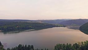 Beautiful aerial view of a lake between green hills with panorama of valley. Beautiful aerial view of a lake between green hills at sunset, with panorama of stock video footage