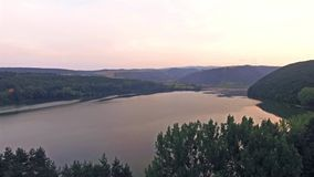 Beautiful aerial view of a lake between green hills at sunset, with panorama of valley stock video footage