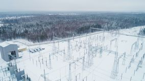 Electrical transmission substation against forest. Beautiful aerial view modern electrical transmission substation against pine winter forest on cold day stock footage