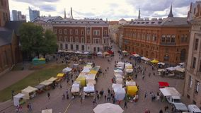 Beautiful aerial view of the Riga old town. Main square Dome square with local market and people preparing for national `Ligo` celebration event stock footage