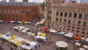 Beautiful aerial view of the Riga old town. Main square Dome square with local market and people preparing for national `Ligo` celebration event stock video footage