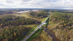 Beautiful aerial view of road bridge over the river surrounded by forest. It is located in the Republic of Karelia. On the bridge one lane in each direction stock video footage
