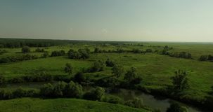 Aerial view of a Russian sunny landscape. Beautiful aerial view of a Russian landscape with fast fields, small river and trees and bushes on a summer sunny day stock video