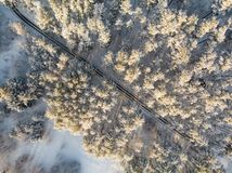 Beautiful aerial view of snow covered pine forests and a road winding among trees. Rime ice and hoar frost covering trees. Winter royalty free stock image