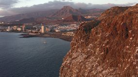 Beautiful aerial view of the south coast of Tenerife and the town of Los Cristianos at sunset stock video