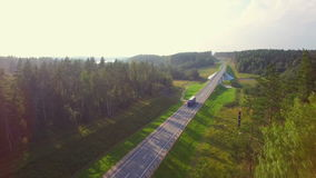 Beautiful aerial view of the truck coming down the road in the woods. stock footage