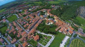 Beautiful aerial view of typical Italian village near mountain, grassy valley. Stock footage stock footage
