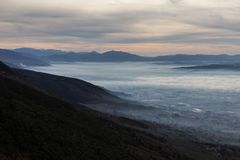 Beautiful aerial view of Umbria valley in a winter morning, with fog covering trees and houses , warm colors in the sky. And layers of hills Stock Photography