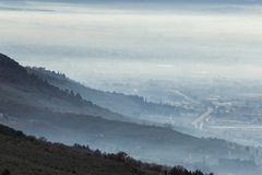 Beautiful aerial view of Umbria valley in a winter morning, with fog covering trees and houses , warm colors in the sky Stock Image