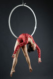 Beautiful aerialist doing acrobatic stunt on hoop Royalty Free Stock Photos
