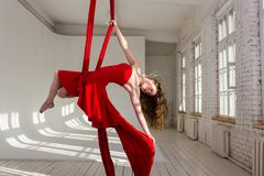 Girl training on aerial silks. Beautiful aerialist girl doing acrobatic and flexible tricks on red aerial silks tissues on white brick and white wall on Stock Photography
