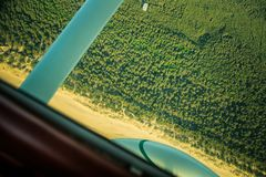 A beautiful aero landscape looking out of a small plane cockpit. Riga, Latvia, Europe in summer. Authentic flying experience in a. Sunny, hazy day. Flying small stock photo