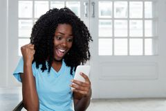 Beautiful africa american woman receiving good news on phone. Indoor at home royalty free stock images
