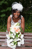 Beautiful african american bride posing in her wedding day with bouquet Stock Images