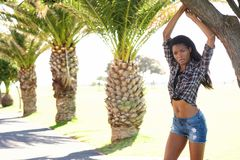 Beautiful african american fashion model next to palm trees Stock Image