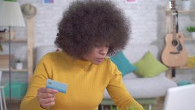 Beautiful african american girl with an afro hairstyle with a Bank card in hand and a laptop in the modern apartment stock video footage